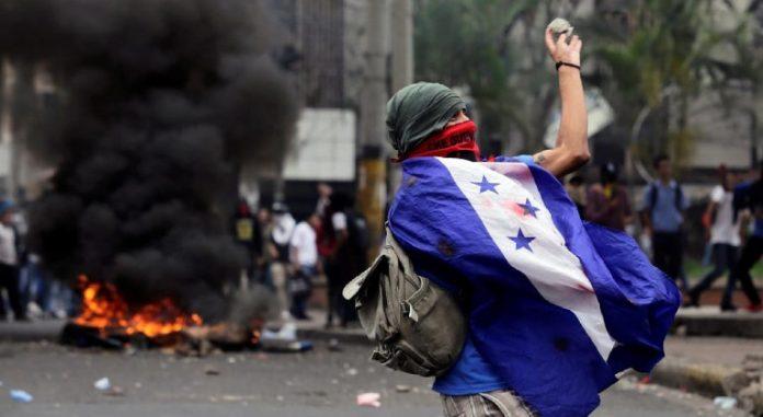 Imagen de archivo - Un jóven hondureño viste la bandera durante una manifestación en julio de 2019