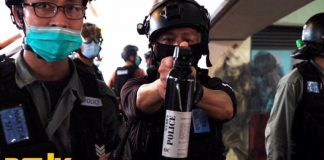 Un funcionario de la policía de Hong Kong apunta su gas pimienta a un periodista | Foto: Sociedad Fotográfica de Hong Kong