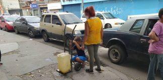 Familias recogiendo agua en las calles de Barquisimeto.